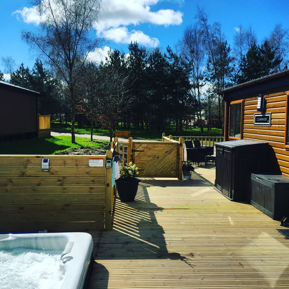 Outside Woodys Lodge, hot tub and terrace area